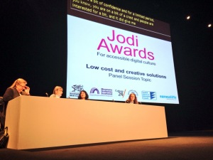 Panel of four speakers in front of a projection 'Low cost and creative solutions - Panel Session Topic'